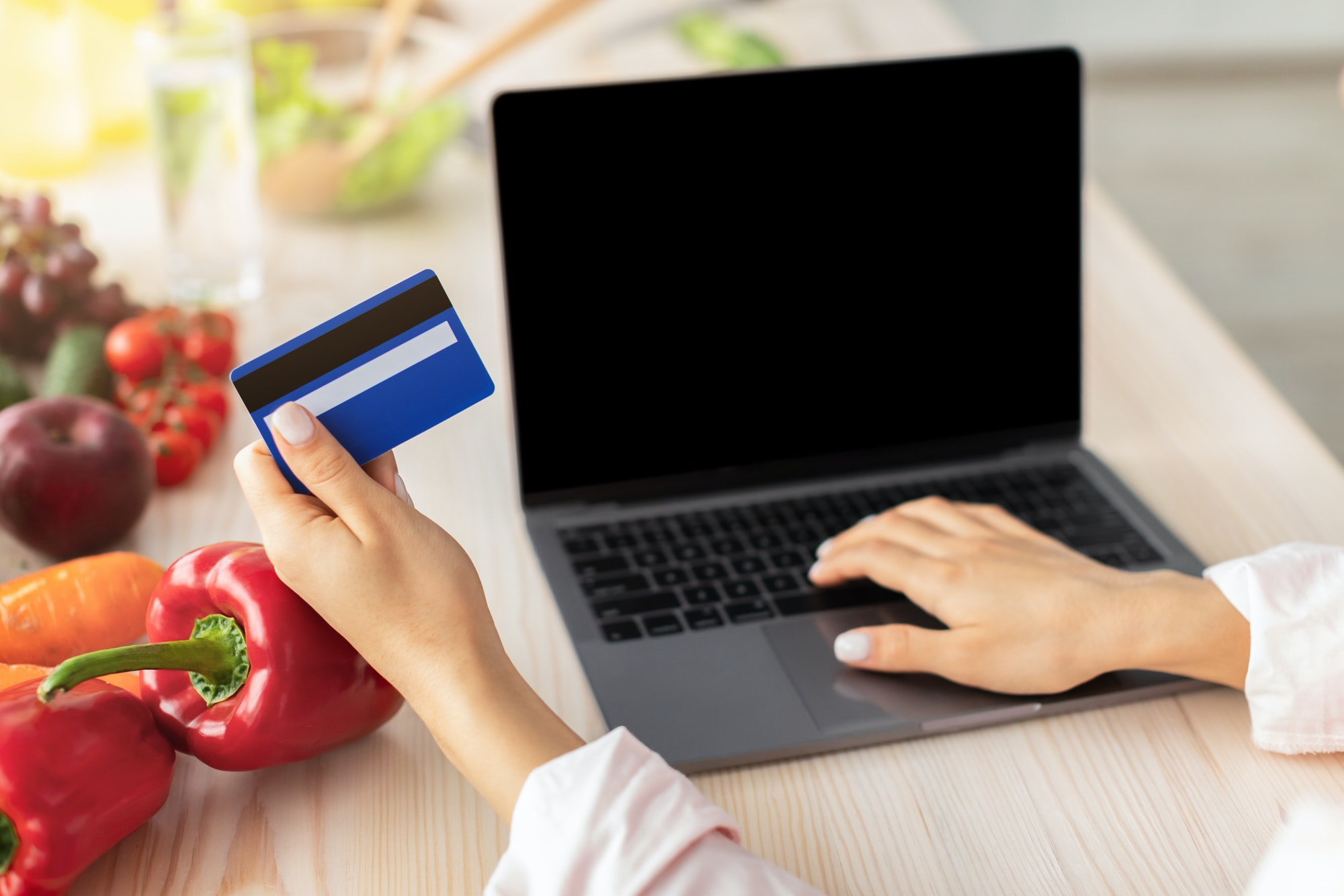 Woman using laptop with in kitchen, holding credit card